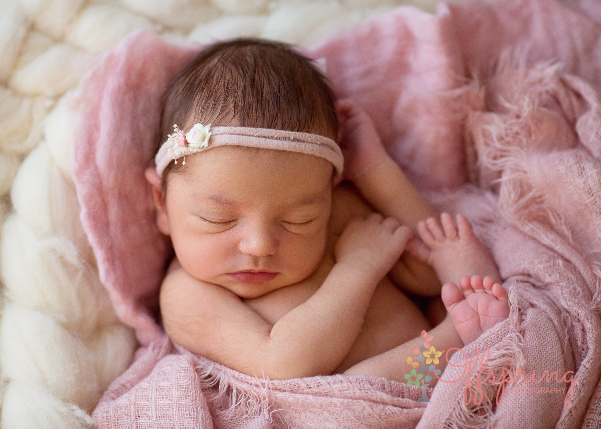 beautiful newborn girl wrapped in pink blanket with matching headband